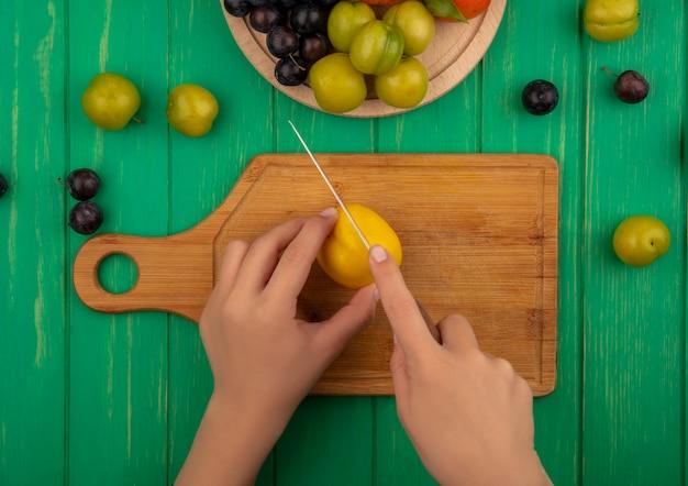 緑の木製の背景に木製キッチンボード上のナイフで黄色の桃を切る女性の手の上から見る 無料写真