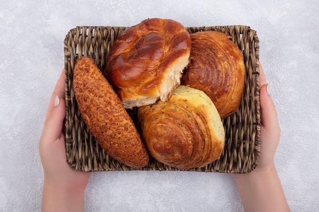 白い背景にゴマパティゴガルのようなパンとバケツを保持している女性の手の上面図 無料写真