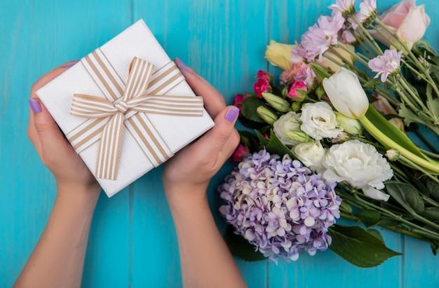 青い木製の背景に分離されたバラgardenziaチューリップデイジーなどの素晴らしい新鮮な花とギフトボックスを保持している女性の手の上面図 無料写真
