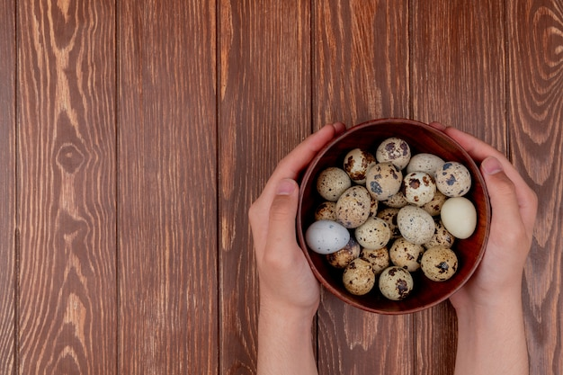 Вид сверху женских рук, держащих деревянную миску с перепелиными яйцами на деревянном фоне с копией пространства Бесплатные Фотографии