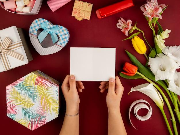 アルストロメリアとハート型のギフトボックスとホワイトチョコレートの赤とかからず色のチューリップの赤いテーブルに白紙のグリーティングカードを置く女性の手の上から見る 無料写真