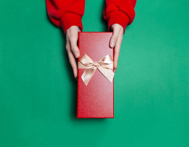 Вид сверху женских рук, держащих подарочную коробку на поверхности зеленого цвета Premium Фотографии