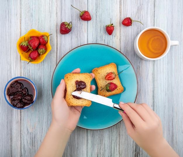 灰色の木製の背景に黄色のボウルに新鮮なイチゴとブループレートにいちごジャムとトーストしたパンを保持している女性の手の上から見る 無料写真