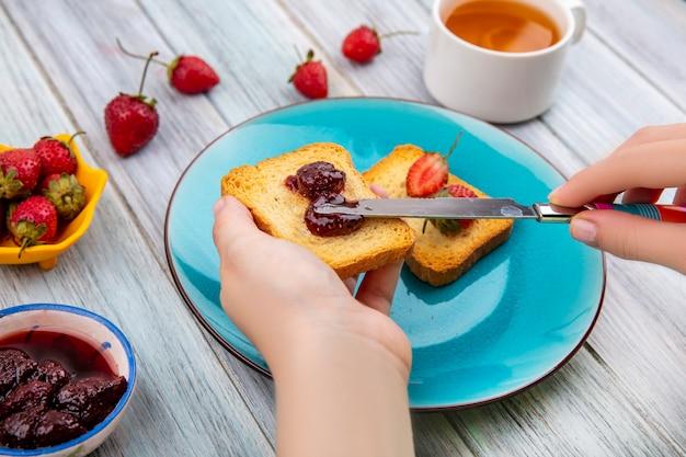 女性の手の平面図は、灰色の木製の背景に黄色のボウルに新鮮なイチゴと青い皿にナイフでパンにいちごジャムを広げる 無料写真