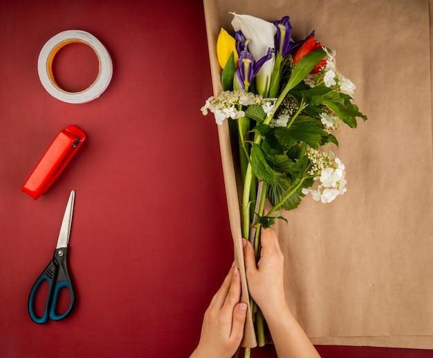 咲くガマズミオランダカイウユリと暗い紫色のアイリスの花の花束をクラフトペーパーとはさみ、ホッチキス、濃い赤のテーブルに粘着テープのロールで包む女性の手の平面図 無料写真