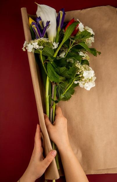 濃い赤のテーブルに咲くガマズミオランダカイウユリとクラフト紙で濃い紫色のアイリスの花の花束を包む女性の手の上から見る 無料写真