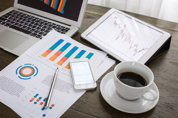 Top view of financial reports next to a cup of coffee Free Photo