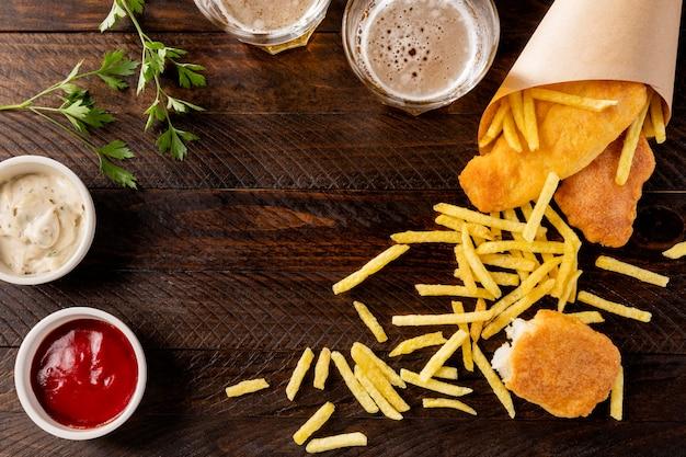 Вид сверху рыбы с жареным картофелем в бумажном рожке с пивом Бесплатные Фотографии