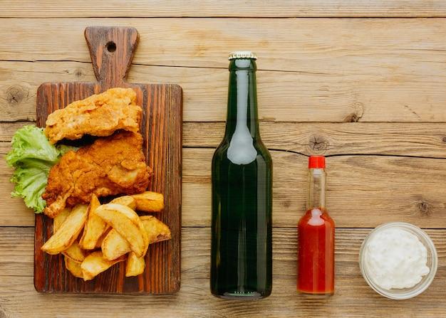 Вид сверху рыбы и чипсов на разделочной доске с пивной бутылкой и кетчупом Premium Фотографии