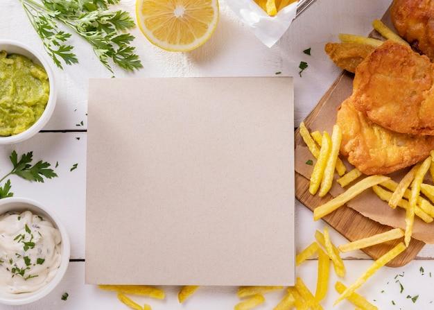 Вид сверху рыбы с жареным картофелем на разделочной доске с картой Бесплатные Фотографии