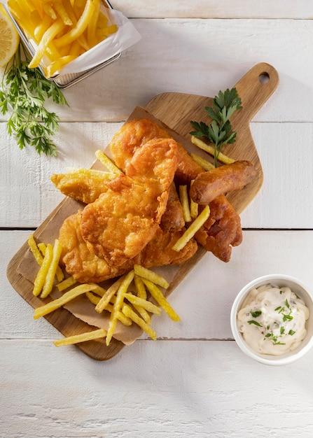 Вид сверху рыбы с жареным картофелем на разделочной доске с соусом Бесплатные Фотографии