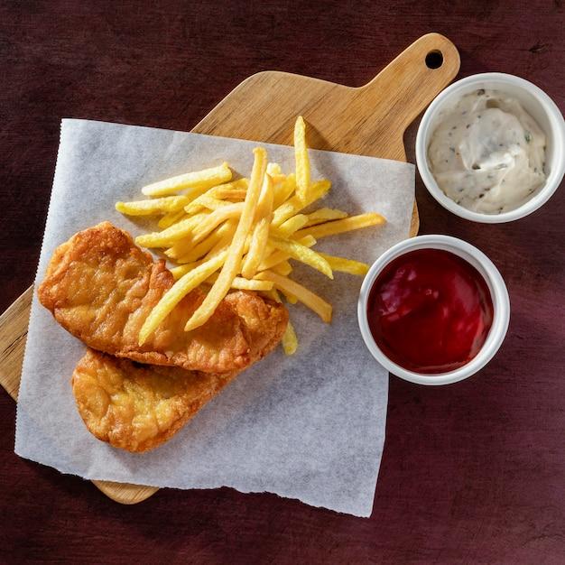 Вид сверху рыбы с жареным картофелем на разделочной доске Premium Фотографии
