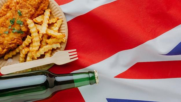 Вид сверху рыбы с жареным картофелем на тарелке с пивной бутылкой и флагом великобритании Бесплатные Фотографии