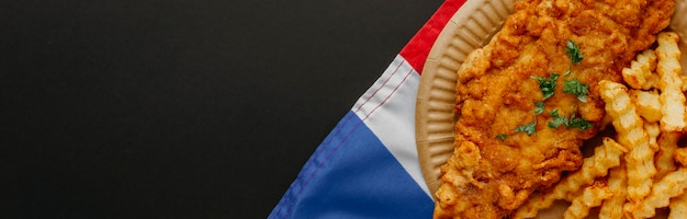 Вид сверху рыбы с жареным картофелем на тарелке с флагом великобритании и копией пространства Бесплатные Фотографии