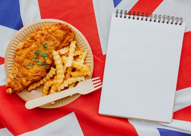 Вид сверху рыбы с жареным картофелем на тарелке с ноутбуком и флагом великобритании Бесплатные Фотографии