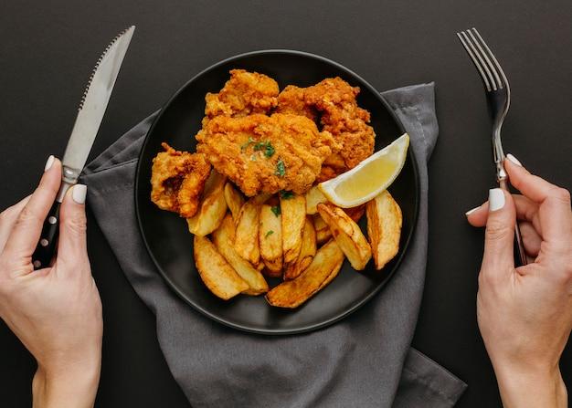 Вид сверху рыбы с жареным картофелем на тарелке с женщиной, держащей столовые приборы Бесплатные Фотографии