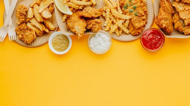 Вид сверху рыбы с жареным картофелем с копией пространства и разнообразных соусов Бесплатные Фотографии