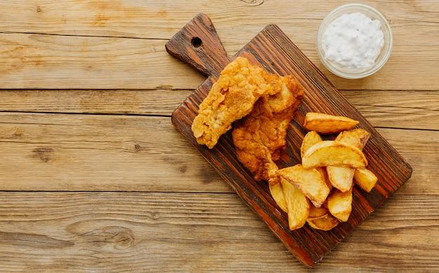 Вид сверху рыбы с жареным картофелем с соусом на разделочной доске Premium Фотографии