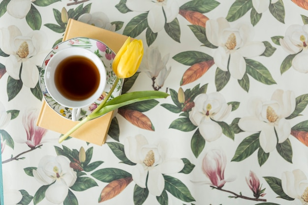 Top view of floral background with tulip, book and tea cup Free Photo