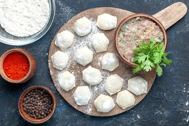 濃い生地の生肉ディナーペストリーにコショウと一緒にミンチミートグリーンを添えた小麦粉生地の上面図 無料写真
