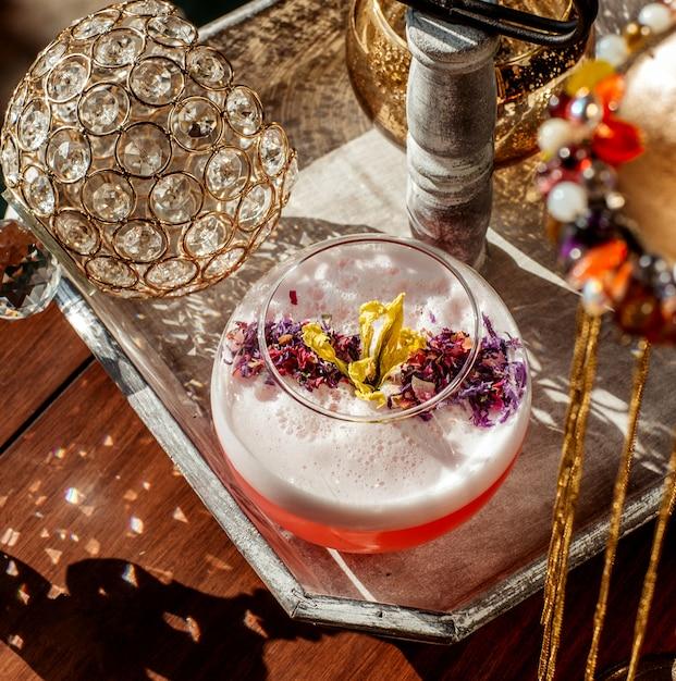 Вид сверху пенного коктейльного бокала, украшенного сухими цветочными лепестками Бесплатные Фотографии
