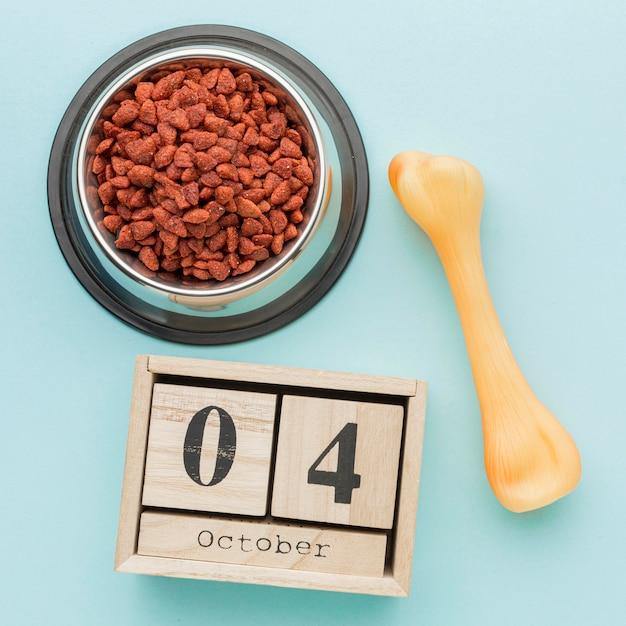 Вид сверху пищевой миски с календарем и костью на день животных Бесплатные Фотографии