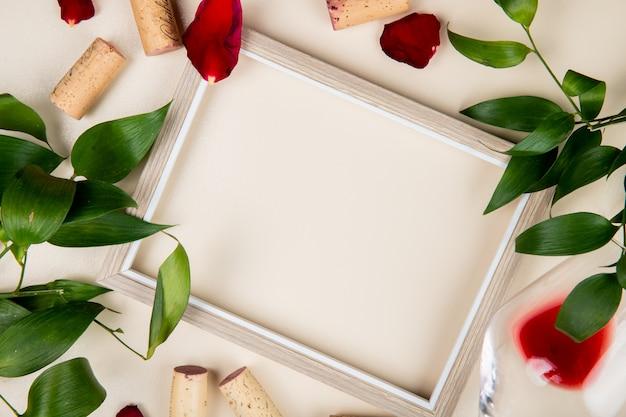 Вид сверху рамы с бокалом красного вина и пробками вокруг на белом украшен листьями и лепестками цветов с копией пространства 1 Бесплатные Фотографии