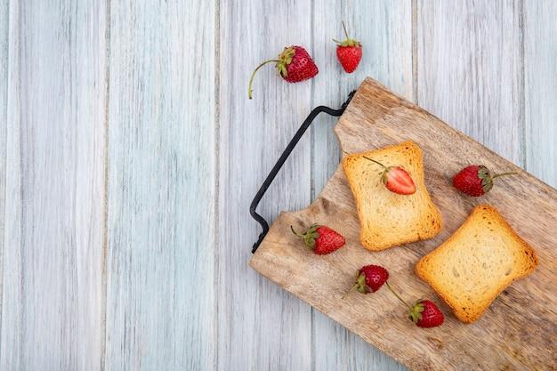 コピースペースを持つ灰色の木製の背景に木製キッチンボード上のトーストしたパンのスライスと新鮮でおいしいイチゴのトップビュー 無料写真