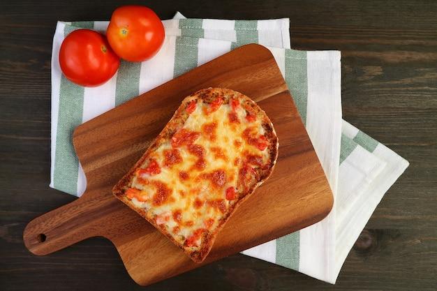 焼きたての自家製ピザトーストとフレッシュトマトのブレッドボードの上面図 Premium写真