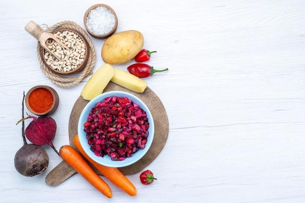 スライスした野菜と生豆にんじんポテトとライトデスクの新鮮なビートサラダ、フードミール野菜の新鮮なサラダの上面図 無料写真