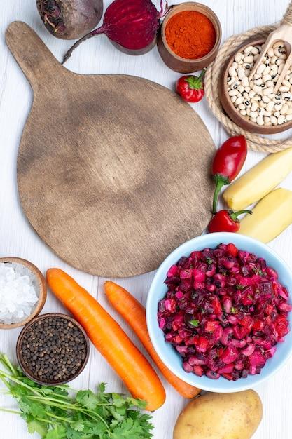 白い机の上に生豆ニンジンポテトと一緒にスライスした野菜と新鮮なビートサラダの上面図、フードミール野菜サラダ 無料写真