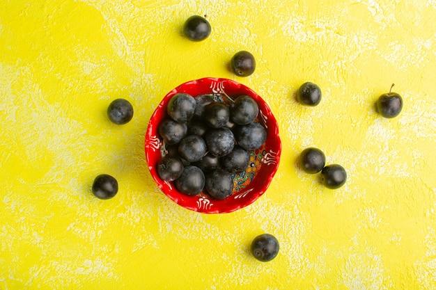 黄色の表面に新鮮なブラックソーンのトップビュー 無料写真