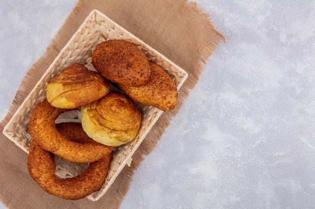 コピースペースと白い背景の上の袋布のバケツの新鮮なパンの上面図 無料写真