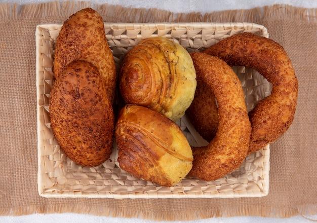 白い背景の上の袋布のバケツに新鮮なパンの上面図 無料写真