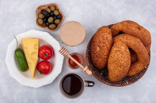 白い背景の上のボウルにチーズトマトとキュウリとバケツの新鮮なパンの上面図 無料写真