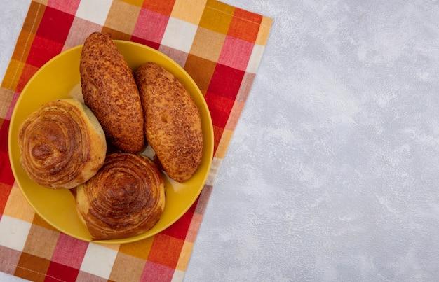 コピースペースと白い背景の上のチェックの布の黄色いプレート上の新鮮なパンの上面図 無料写真