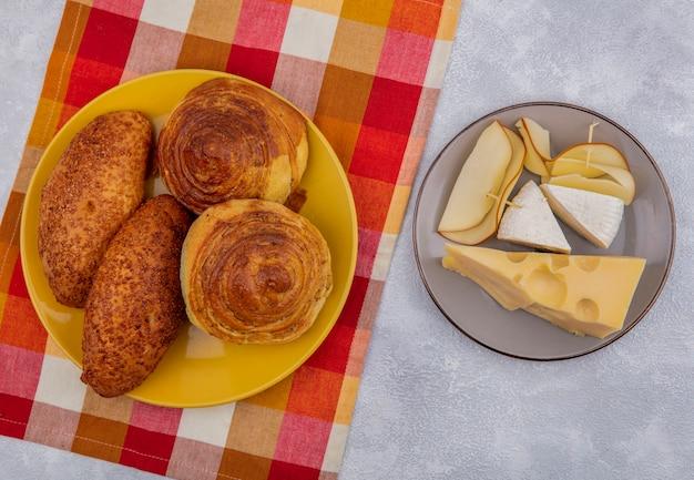 白い背景の上の灰色のプレート上のさまざまな種類のチーズとチェックされた布の黄色いプレート上の新鮮なパンの上面図 無料写真