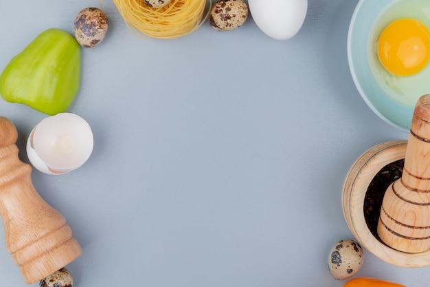 コピースペースと白い背景の上の塩のシェーカーとひびの入った卵の殻と青いボウルに新鮮な鶏の卵黄と白の平面図 無料写真