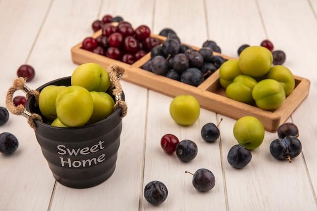Вид сверху свежих фруктов, таких как зеленая вишня и терн на деревянном разделенном подносе с зеленой алычой на корзине на белом фоне Бесплатные Фотографии