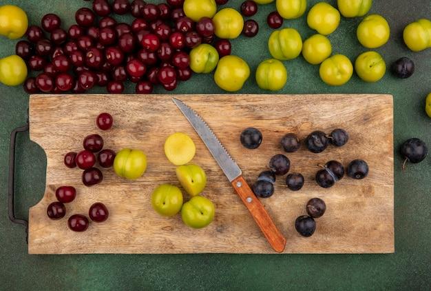 Вид сверху на свежие фрукты, такие как красная вишня, зеленая алыча, темный фиолетовый терн на деревянной кухонной доске с ножом с красной вишней, изолированной на зеленом фоне Бесплатные Фотографии