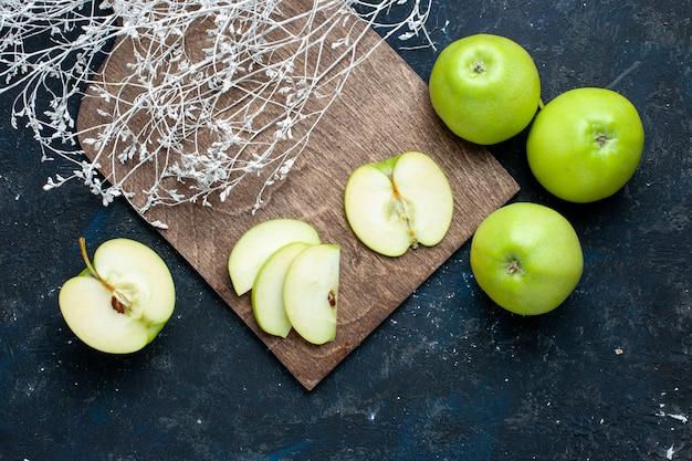 Вид сверху на композицию из свежих зеленых яблок с разрезанными на половину ломтиками, выложенными на темном столе, свежие спелые фрукты Бесплатные Фотографии