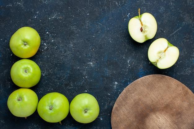 Вид сверху на композицию из свежих зеленых яблок с половинчатыми ломтиками, выложенными на темных, свежих спелых фруктах Бесплатные Фотографии