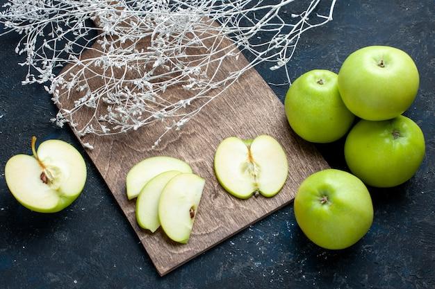 Вид сверху на композицию из свежих зеленых яблок с разрезанными на половину ломтиками, выложенными на темном, фруктовом свежем спелом Бесплатные Фотографии