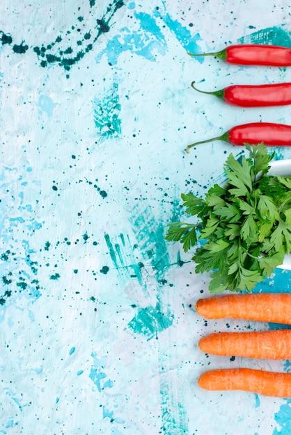 Вид сверху на свежую зелень, изолированную внутри тарелки, с пряным красным перцем и морковью на ярко-синем, зеленом листе Бесплатные Фотографии