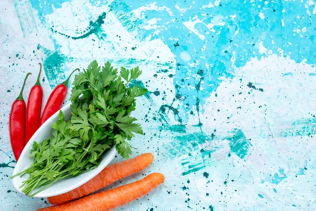 明るい青、緑の葉製品の食品の食事にスパイシーな赤唐辛子とニンジンとプレートの内側に分離された新鮮な緑の上面図 無料写真