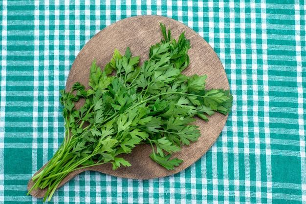 茶色の木製の机の上に隔離された新鮮な緑と明るい青、緑の葉の食べ物の食事の上面図 無料写真