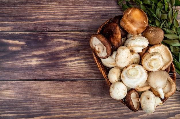 Взгляд сверху свежих грибов в плетеной корзине на деревенской древесине с космосом экземпляра Бесплатные Фотографии