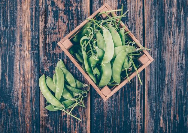 木製の箱と脇に並んでいる新鮮なエンドウ豆のトップビュー 無料写真