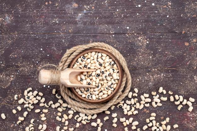 茶色のボウルの中の新鮮な生豆の上面図で、茶色の食品生豆ハリコット全体に広がっています 無料写真