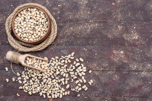 茶色の机の上のロープ、食品生豆ハリコットと茶色のボウルの中の新鮮な生豆の上面図 無料写真